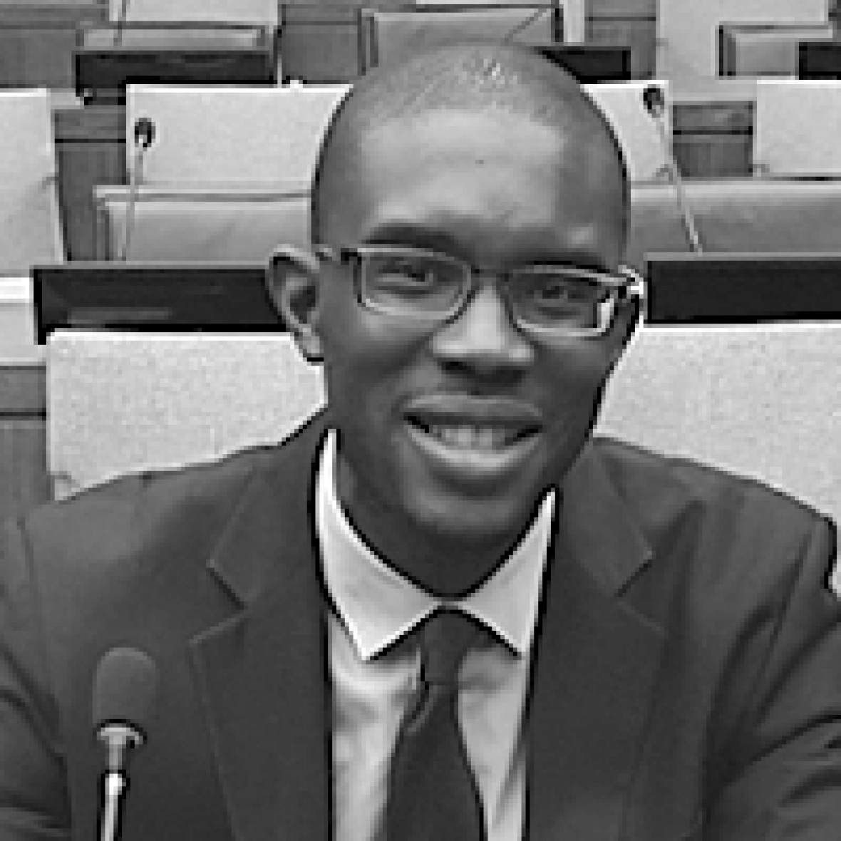 head and shoulders of Watson Fellow Lincoln Ajoku smiling at camera, wearing a suit and tie, in black and white